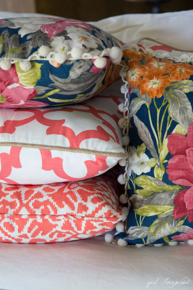 stacked coral, white and blue floral pillows on white couch