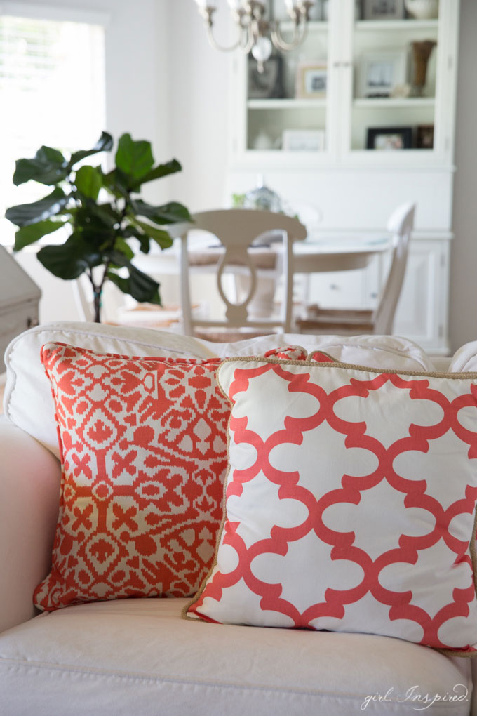 coral and white pillows on white couch with kitchen table and hutch in background
