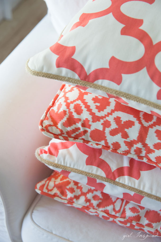 close up of coral and white patterned pillows stacked on white couch