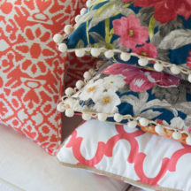 stacked pillows - coral and blue floral on a white couch