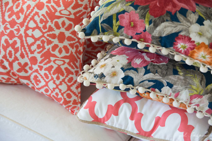 stacked blue floral and coral/white pillows on white couch