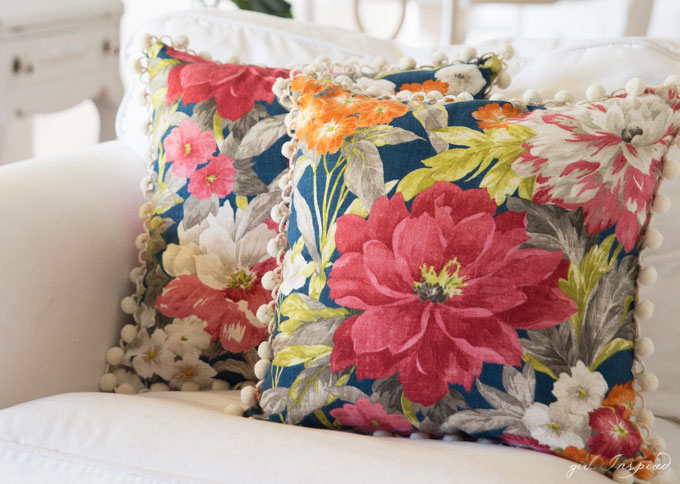 two blue floral pillows on white couch