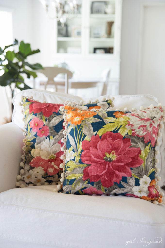 two blue floral pillows on white couch with kitchen table and hutch in background