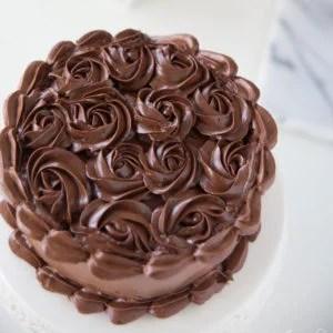 dark chocolate buttercream piped swirls and border on white cake platter
