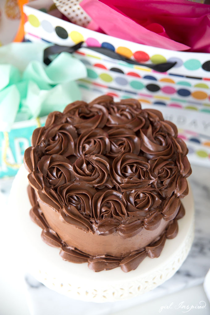 dark chocolate frosting piped in swirls on cake on white platter with birthday gift bags in background