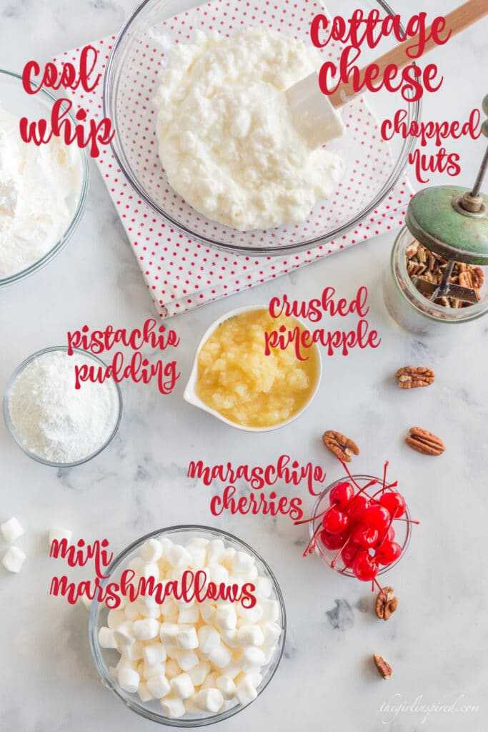 ingredients with text overlay: cottage cheese, chopped nuts, crushed pineapple, mini marshmallows, pudding mix, Cool Whip, and maraschino cherries in individual bowls