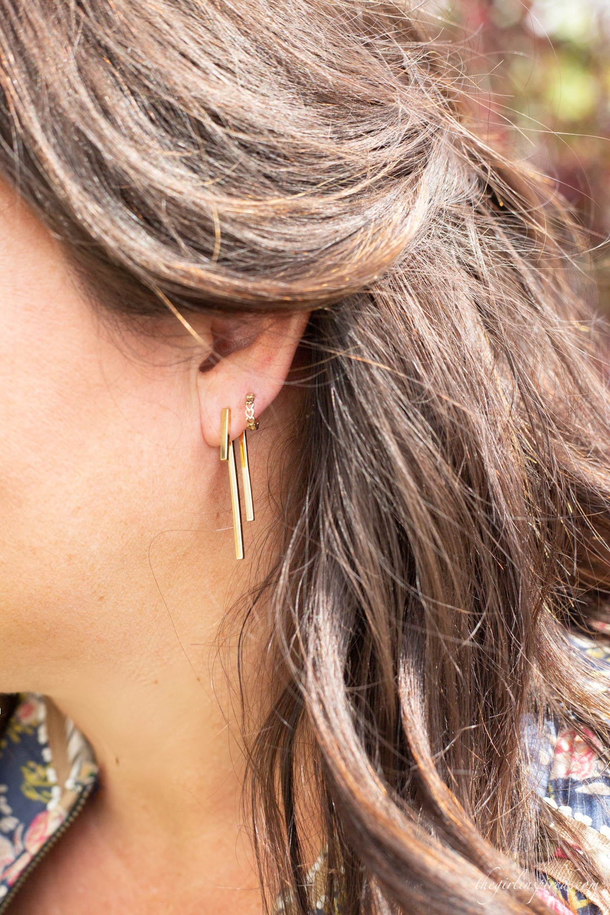 closeup photo of gold bar earrings and tiny gold heart hoops on earlobe with brunette hair