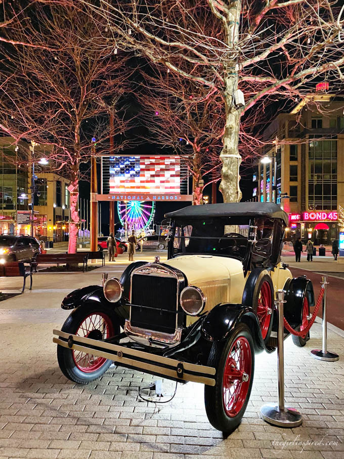 Nighttime view of old Ford truck on street display with statues, trees, and illuminated American flag in the background.