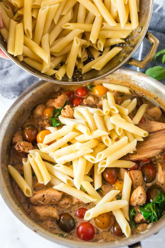 penne pasta pouring into chicken and tomato saucepan mixture