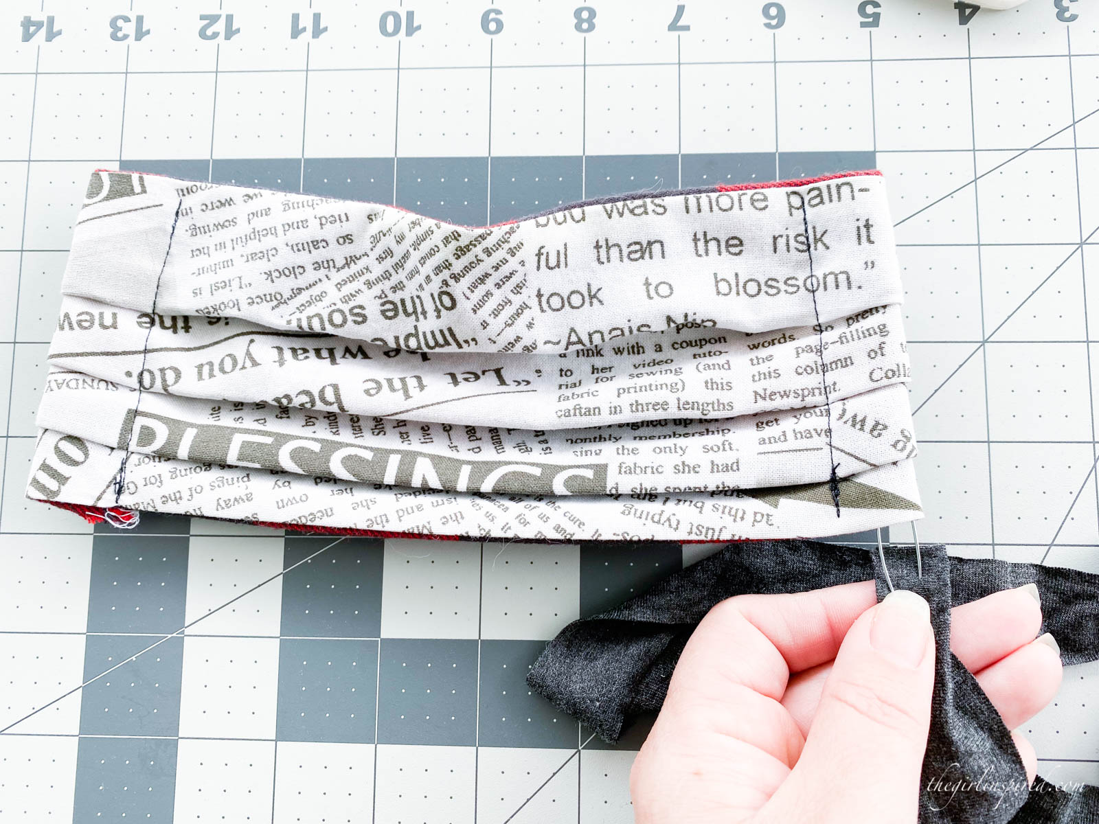 safety pin and strap inserted into side of serged fabric mask on rulered mat