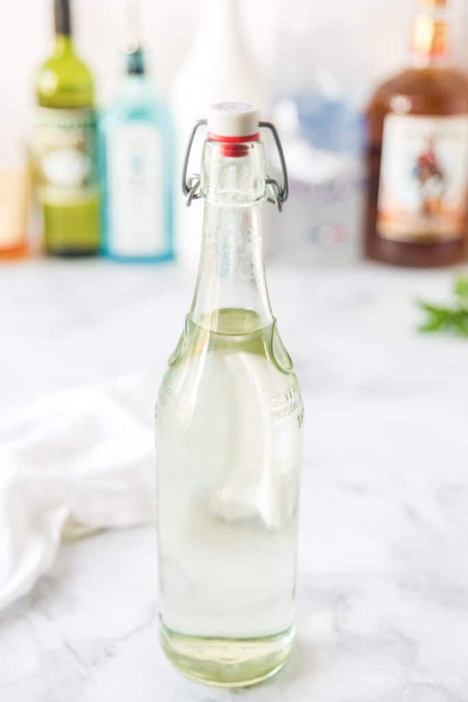 tall glass bottle of simple syrup with other alcohol bottles in the background