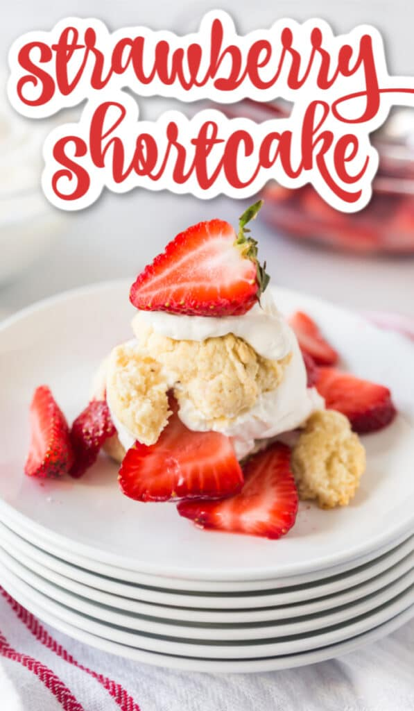 Strawberry shortcake biscuits, whipped cream, and fresh strawberries on a stack of white plates with text overlay