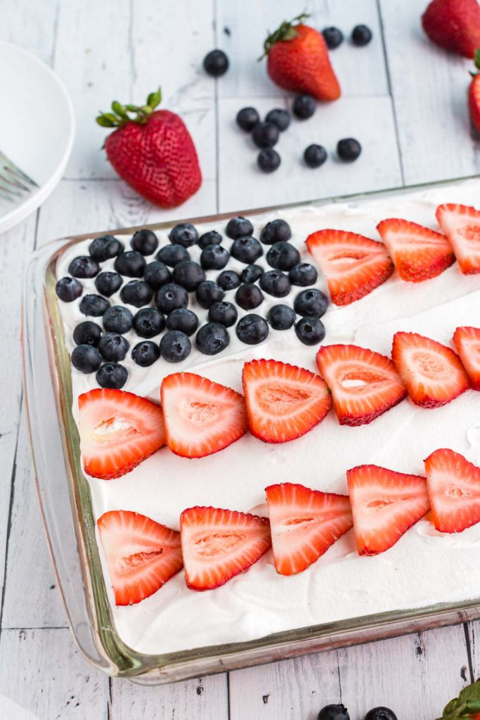 sliced strawberries and blueberries forming a flag on top of cake