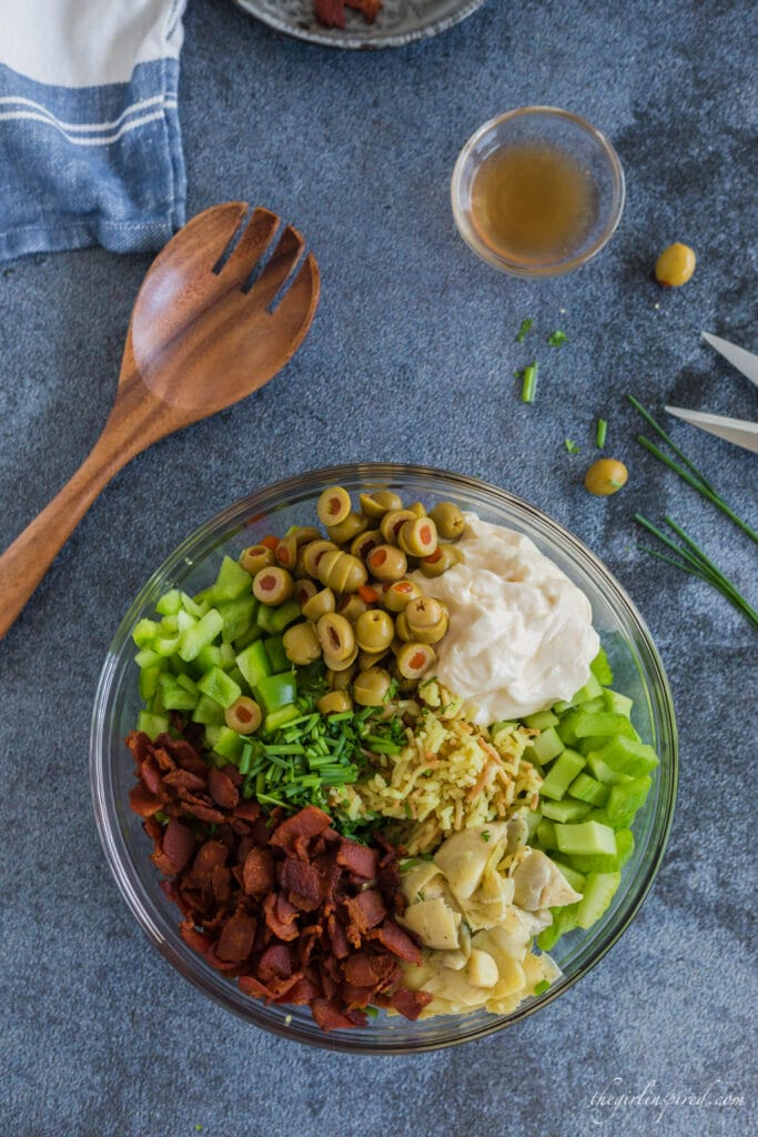 overhead view of glass bowl with separated ingredients in bowl: green olives, sour cream, bell pepper, celery, artichokes, bacon, and chives, wooden serving spoon