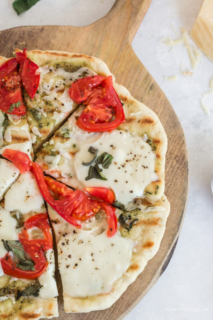 pizza with grill lines, tomatoes, basil, and melted cheese on wooden board with parmesan, basil leaves, and grey linen in background