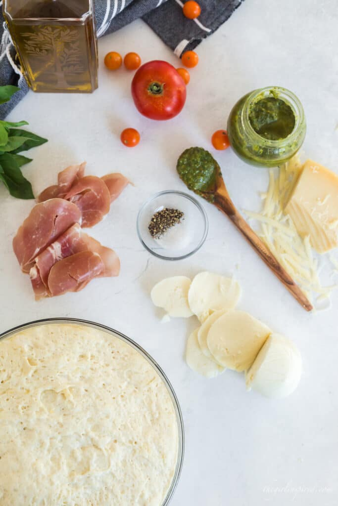 pizza dough in glass bowl, olive oil, prosciutto, basil, tomatoes, salt and pepper, pesto and wooden spoon in background