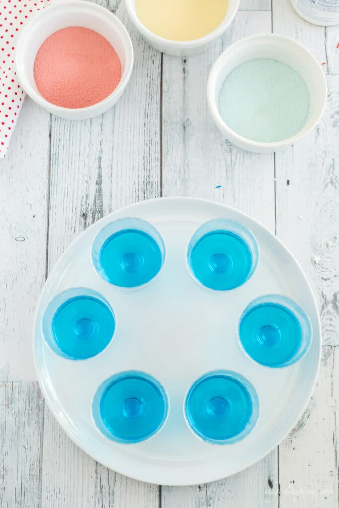 overhead photo of white plate with cups of blue jello, white bowls with red jello powder, blue jello powder, and sweetened condensed milk