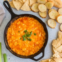 overhead photo of baked buffalo chicken dip with green onions on top, chips and toasted baguette slices, celery sticks