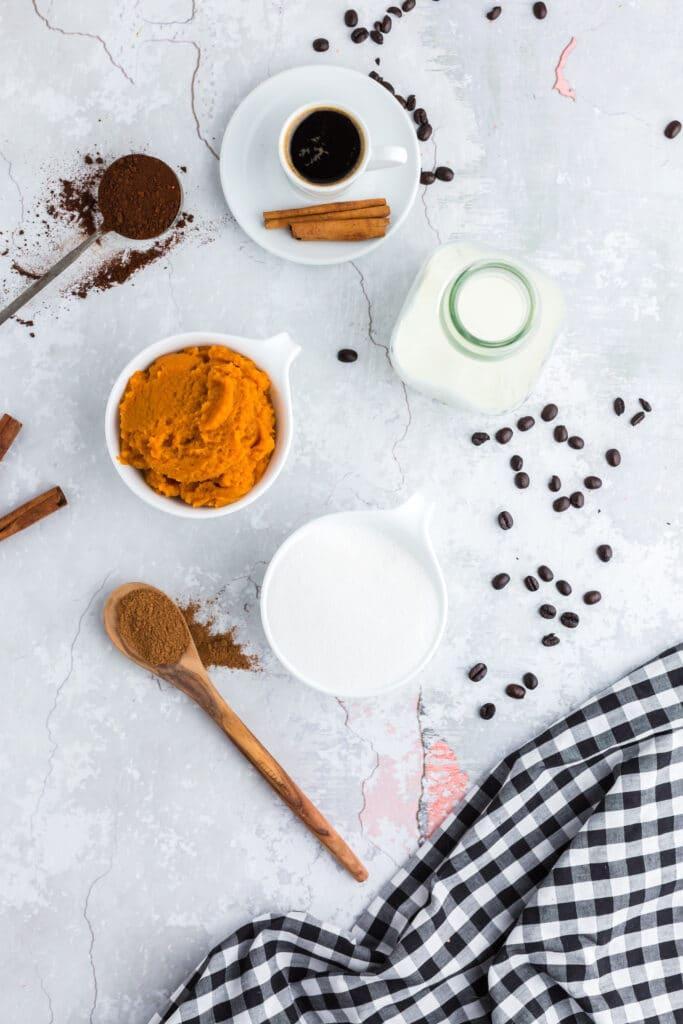 overhead view of pumpkin spice latte ingredients: pumpkin, sugar, cinnamon on wooden spoon, coffee granules, espresso, and milk