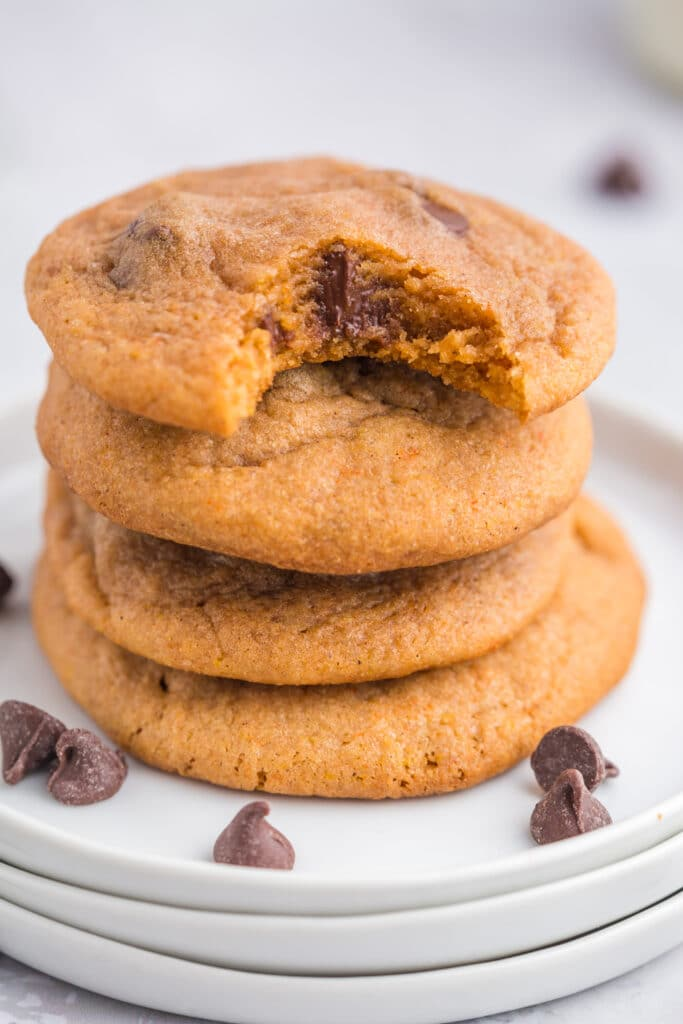 pumpkin chocolate chip cookies stacked on white plates with a bite taken out of the top cookie