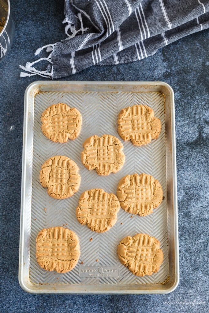 overhead view of peanut butter cookies on baking sheet on blue background