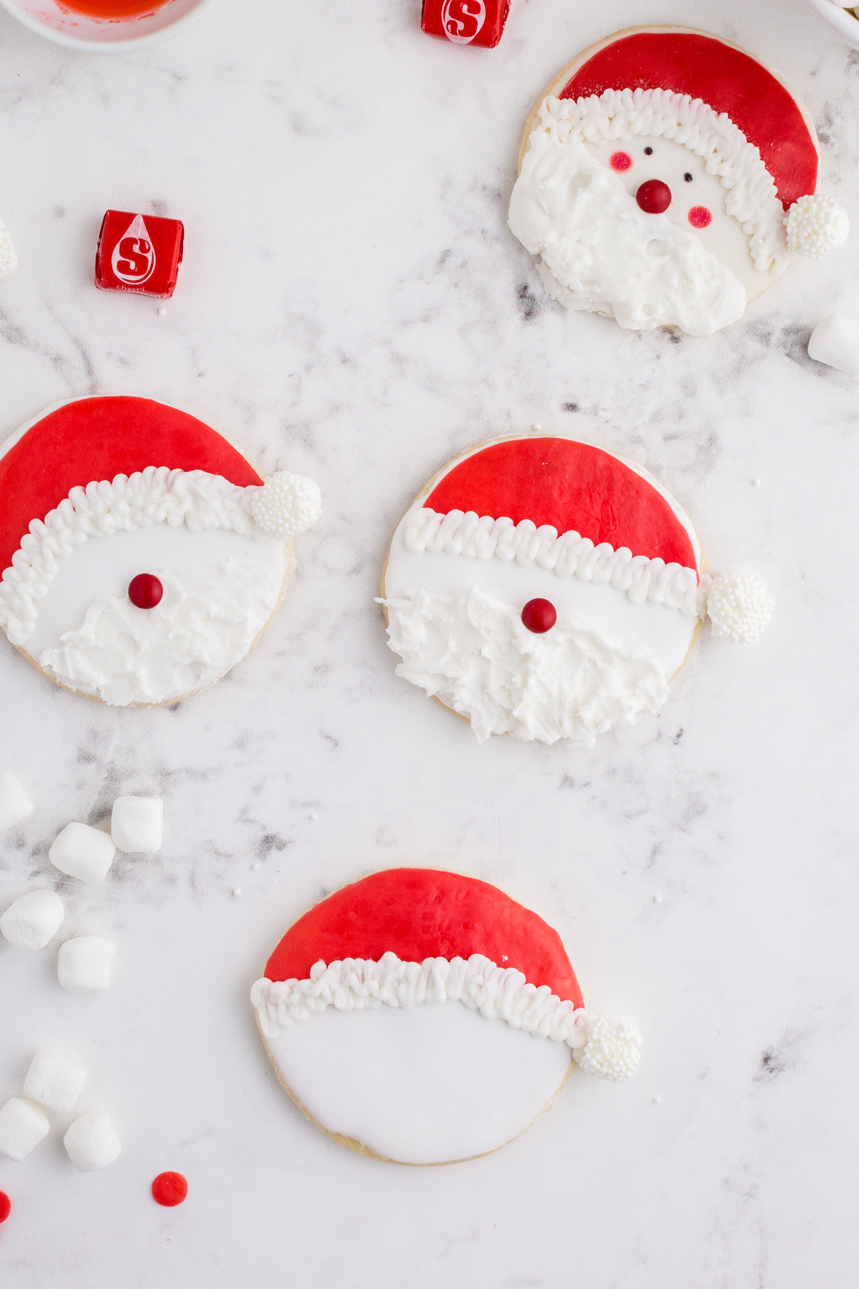 noses and beards added onto the Santa cookie faces