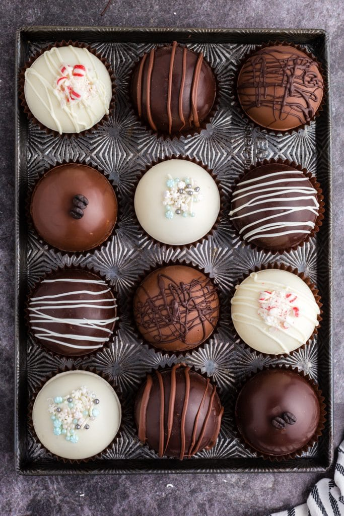 dark, milk, and white chocolate hot chocolate bombs decorated with coffee beans, gold shimmer, sprinkles, or chocolate drizzle displayed on baking sheet