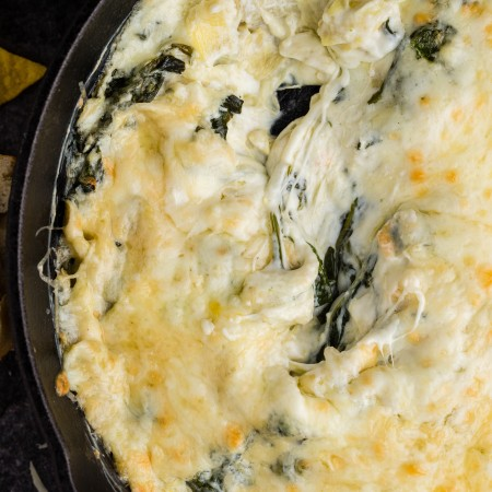 close up of cheesy spinach artichoke dip cooked in skillet