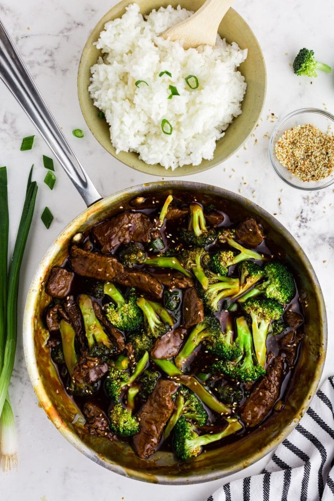 beef and broccoli in saute pan with bowl of rice, sesame seeds, and green onions