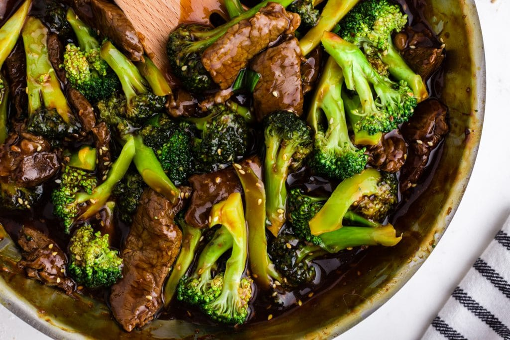 beef and broccoli in saute pan with wooden spoon