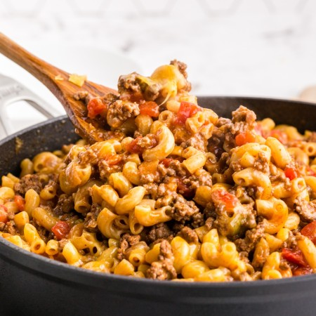 Chili Mac in saute pan with wooden spatula taking a scoop