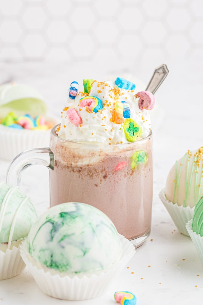 clear mug of hot chocolate with whipped cream, gold sprinkles, and Lucky Charms on top, marbled hot chocolate bombs sitting beside mug