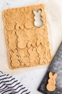 bunny cookie cutter pressed into peanut butter mixture with many shapes cut
