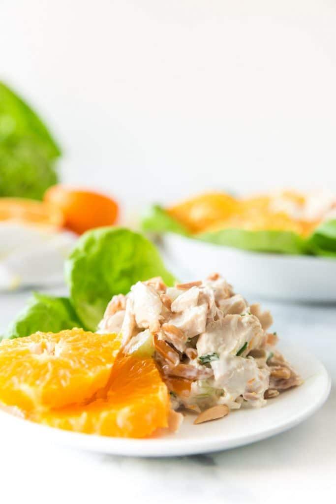 chicken salad and orange slices on white plate