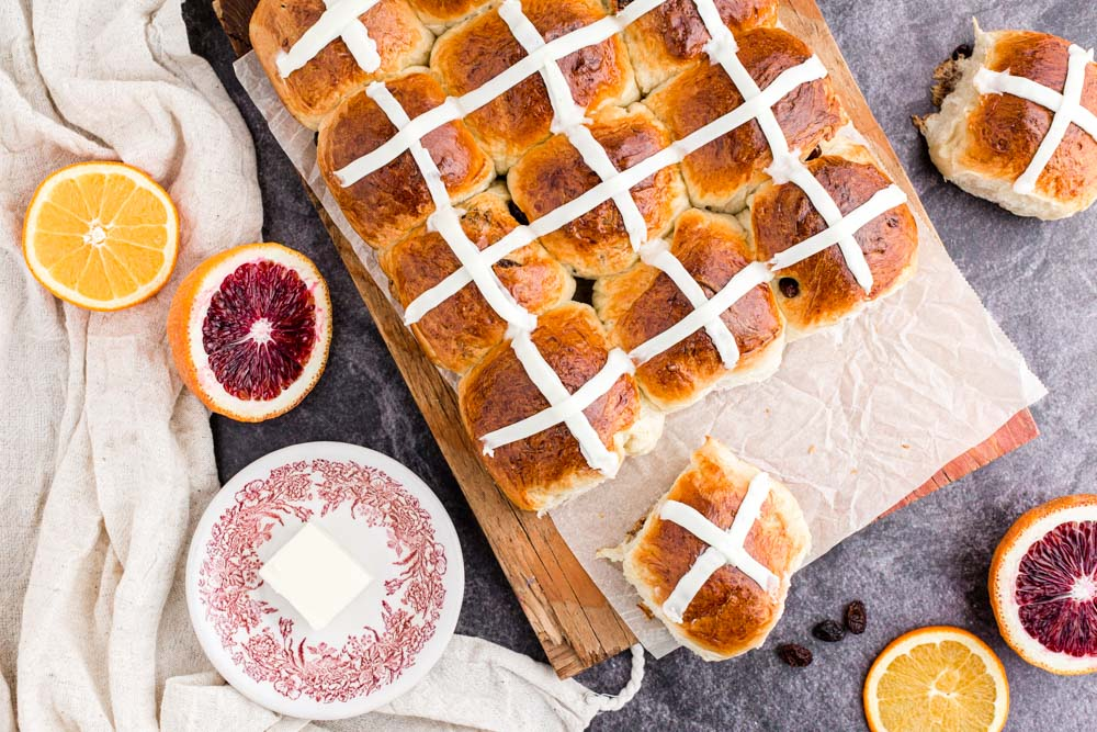 overhead of hot cross buns on a cutting board with butter dish and orange slices scattered around