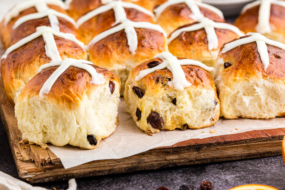 hot cross buns on parchment paper and wooden cutting board