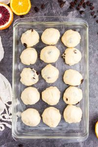 hot cross bun dough rolled into balls and placed in baking dish