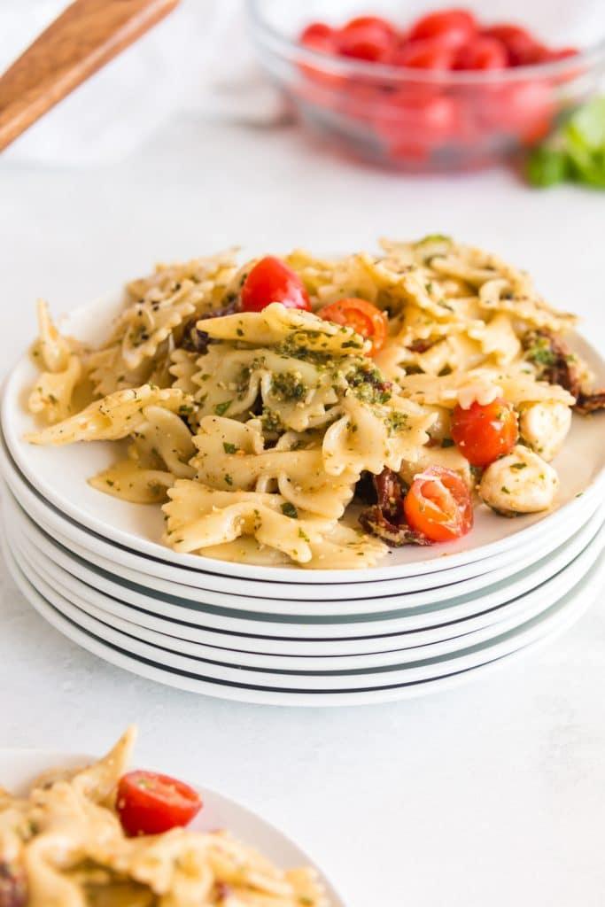 pesto pasta salad piled on a stack of white plates