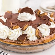 Glass pie dish filled with Peanut Butter Chocolate Ice Cream Pie on marble counter top