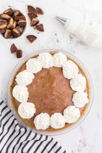 Glass pie dish with graham cracker crust filled with peanut butter chocolate ice cream decorated with whipped cream , bowl with cut peanut butter cups, grey and white striped linen on marble counter top