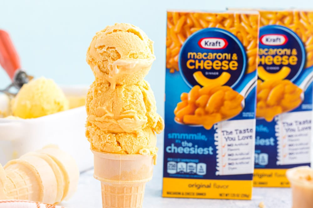 scooped cheese ice cream on a cone with boxes of mac and cheese in background