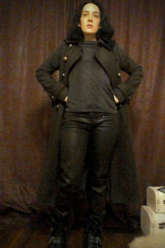 Khaki military style coat, dark top, wax coated black trousers & leather biker boots