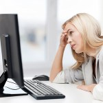 Frustrated blonde woman sitting at a computer