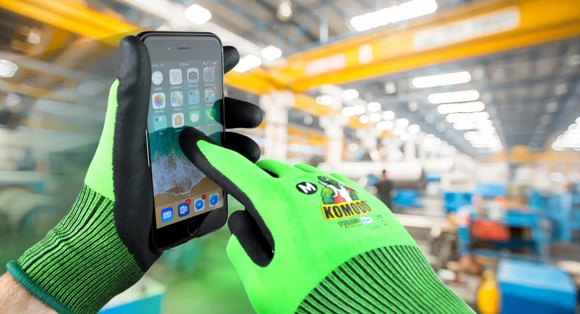 person wearing protective gloves using touch screen device