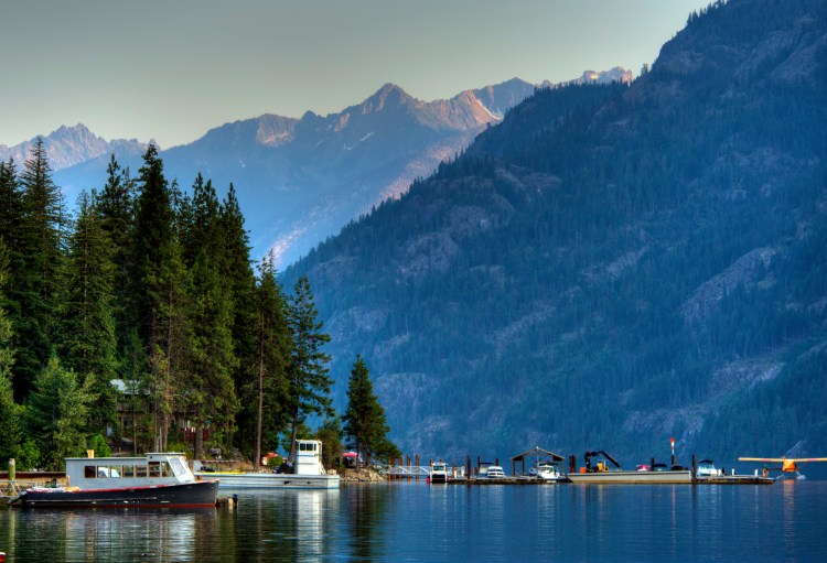 Lake with boats and mountainous backdrop inside North Cascades National Park