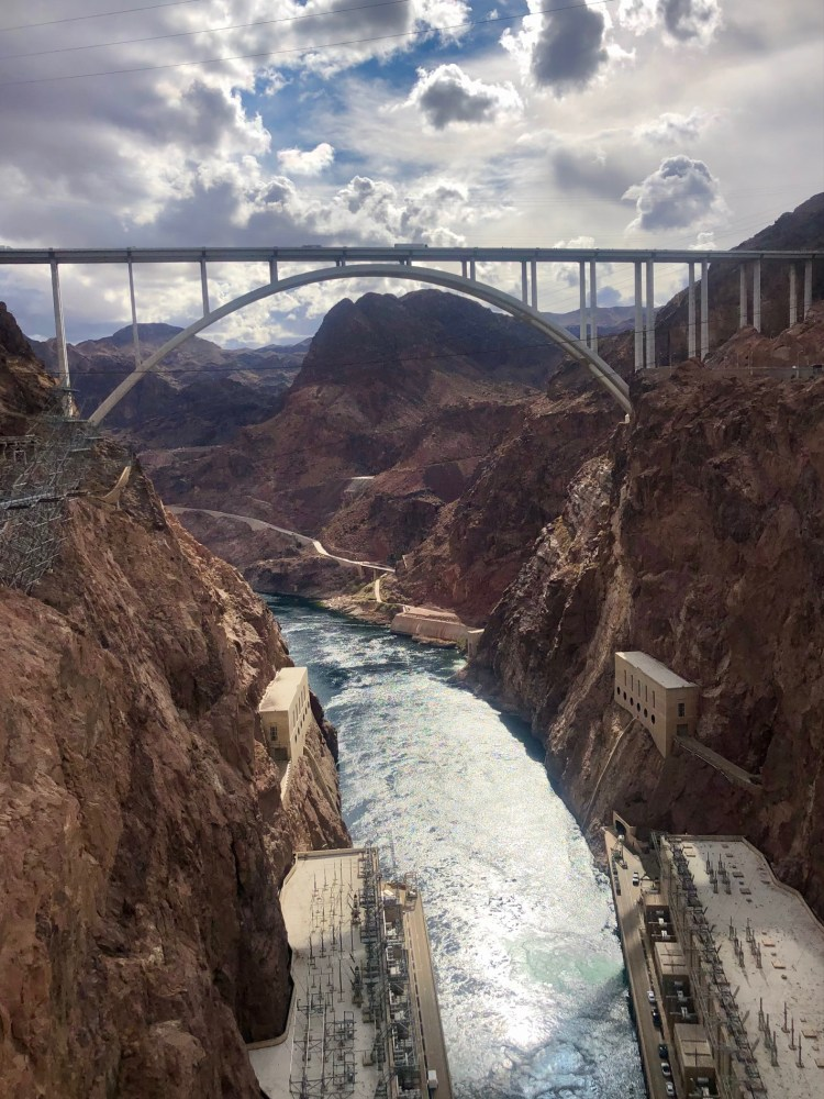 View from Hoover Dam looking out over the Colorado River and the bridge that traverses over it.