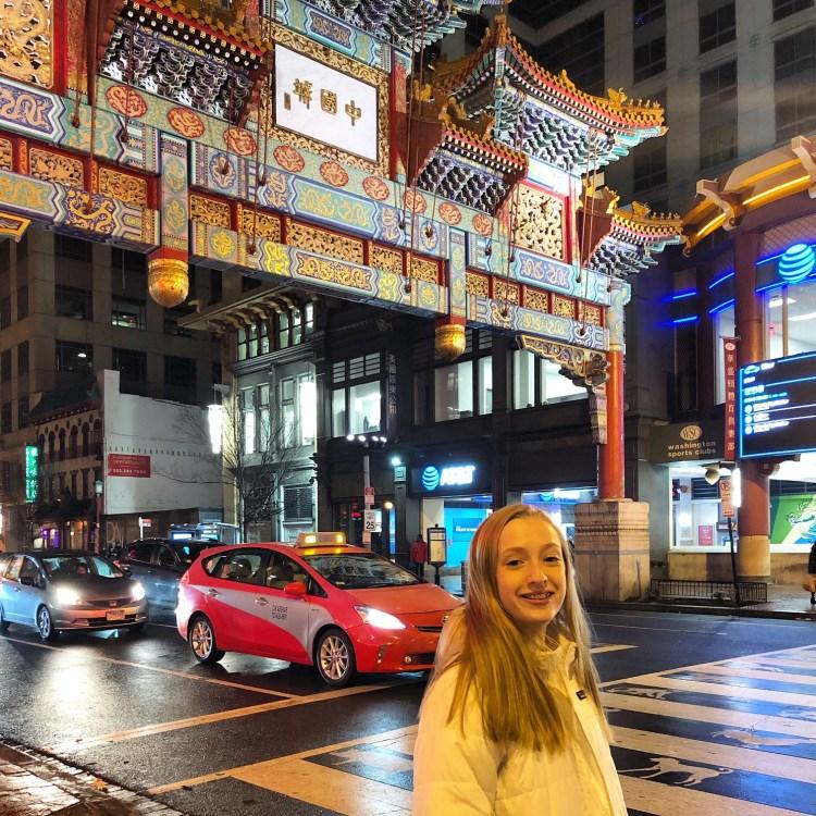 Teenage girl under Chinatown arch in Washington D.C. at night