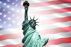 Statue of Liberty in front of a US Flag