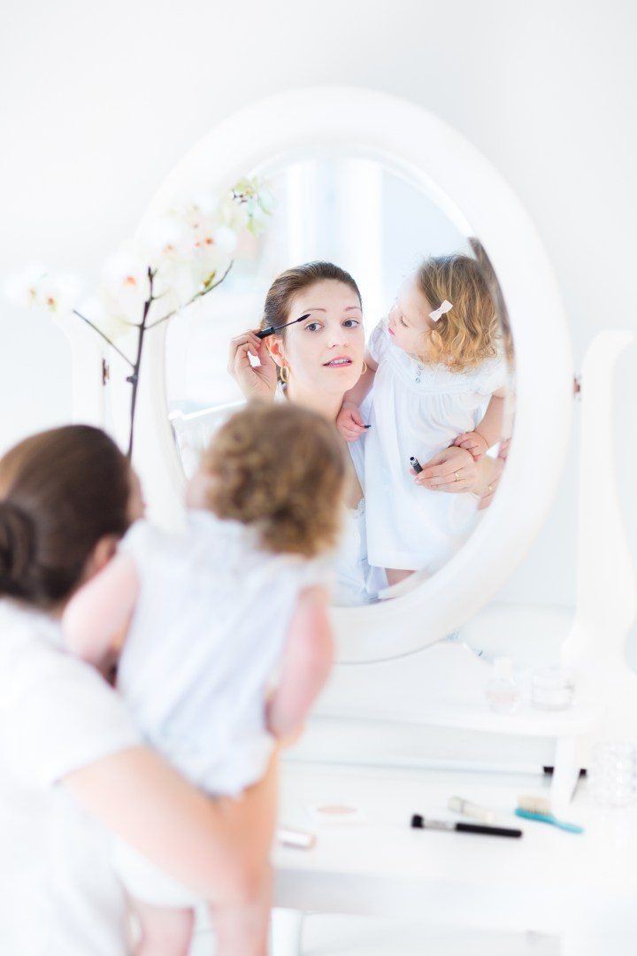 Beautiful young woman applying make up with her toddler daughter