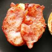 Cooked bacon on an English muffin